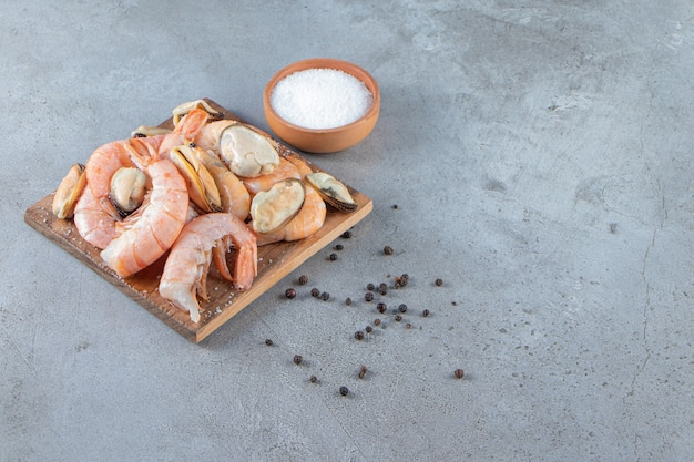 Cozze e gamberi su un tagliere accanto al sale, su fondo di marmo.
