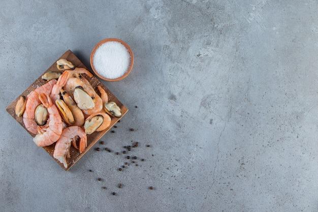 Cozze e gamberi su un tagliere accanto al sale, sullo sfondo di marmo.