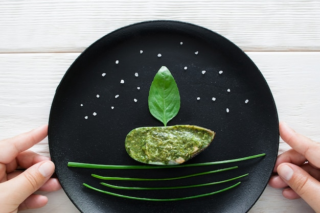 Mussel served with herbs on black plate