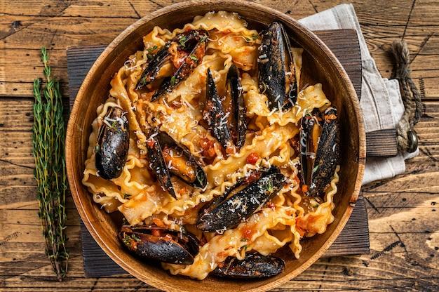 소박한 나무 접시에 토마토 소스를 곁들인 홍합과 조개 마팔딘 파스타. 나무 배경입니다. 평면도.