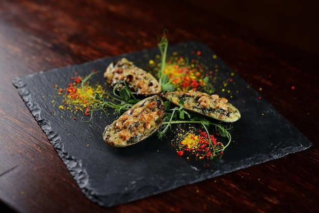 Mussels baked under cheese with pine nuts. on a black board