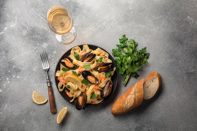 Mussels, bread toasts and white wine on stone table. top view with copy space.