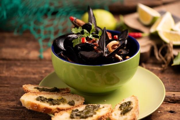 파슬리를 곁들인 화이트 와인 소스로 요리한 홍합 클로즈업