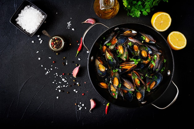 Mussels cooked in wine sauce with herbs in a frying pan on a black background