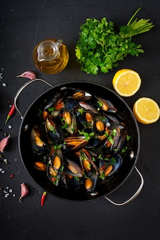 Mussels cooked in wine sauce with herbs in a frying pan on a black table. flat lay. top view.
