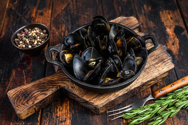 Mussels cooked with white wine sauce in a pan with herbs