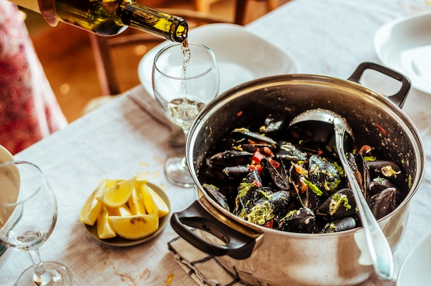 Mussels in copper pot and white wine on table. top view.