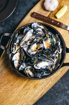 Mussels in a creamy garlic sauce in a black metal plate on a wooden board.