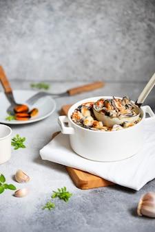 ムール貝のクリームソースと白ワインソース。鍋と白い鍋にニンニクとハーブを添えてください。シーフードのグルメ料理。明るい灰色の背景。正面図