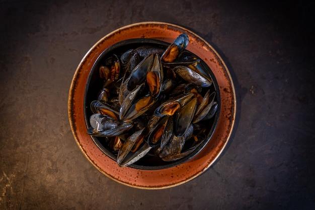 オレンジ色のプレートで、黒の背景にソースのムール貝
