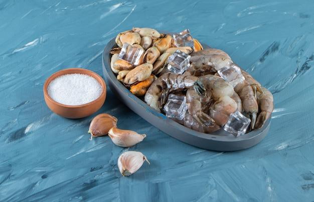 Мидии, креветки и кубик льда на деревянной тарелке рядом с солью и чесноком на мраморной поверхности.