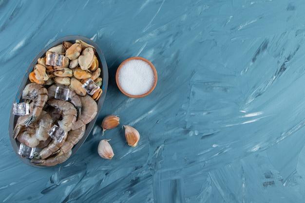 Cozze, gamberi e cubetto di ghiaccio su un piatto di legno, sullo sfondo di marmo.