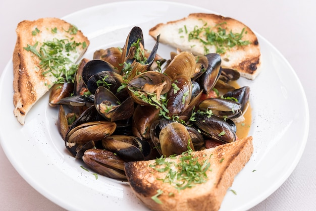 Mussels in sauce with parsley,  french toast and lemon. seafood. clams in the shells.