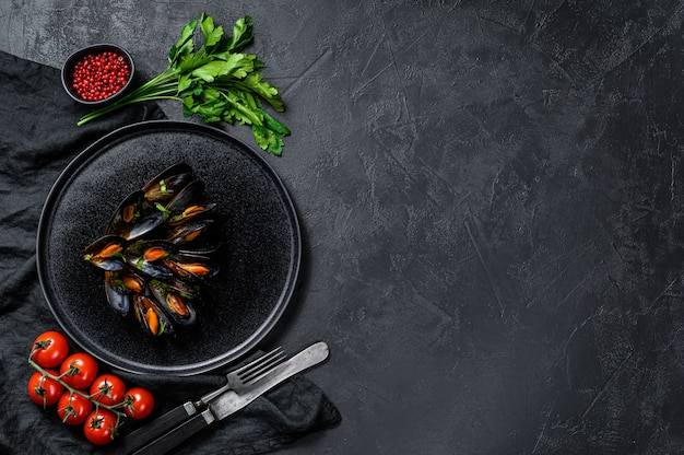 Mussels in tomato sauce decorated with parsley and cherry tomatoes. black background. top view. space for text