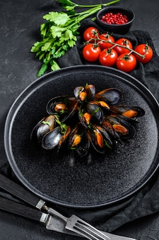 Mussels in tomato sauce decorated with parsley and cherry tomatoes. black background. top view