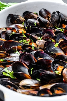 Mussels in tomato sauce with parsley and herbes in italian style. black background. top view
