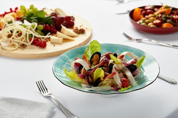 サラダ付きムール貝のボンゴレ、白ワインソースで調理したムール貝、各種チーズやその他の軽食に囲まれたテーブルの上のムール貝の前菜。