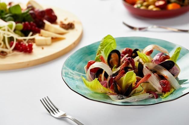 양상추와 함께 접시에 담긴 홍합 봉골리, 화이트 와인 소스로 요리한 홍합, 요리사가 제공하는 해산물.