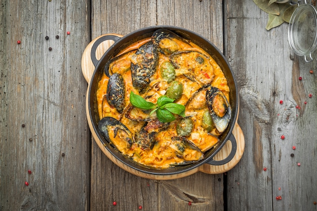 Mussels with cheese sauce, in a frying pan