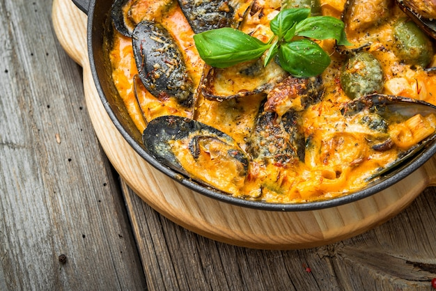 ムール貝とチーズソース、フライパン、木製の背景