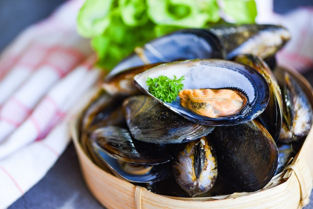 Мидии с зеленью лимона на поваре готовят еду. свежие морепродукты из морепродуктов в ресторане мидии, ракушка на бамбуковом пароварке