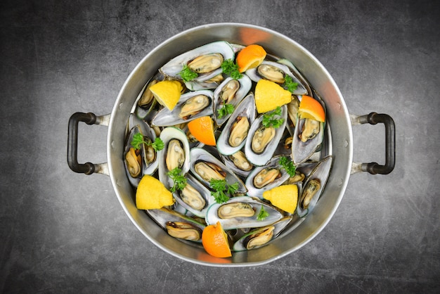 Mussels with herbs in pot with orange lemon parsley tomato in the table setting