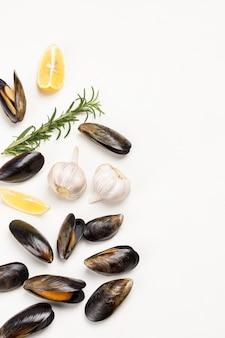 На столе разбросаны мидии с лимоном, чесноком и розмарином. морепродукты из моллюсков. плоская планировка