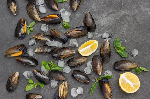 Mussels with lemon and ice, mint are scattered on table. shellfish seafood. flat lay