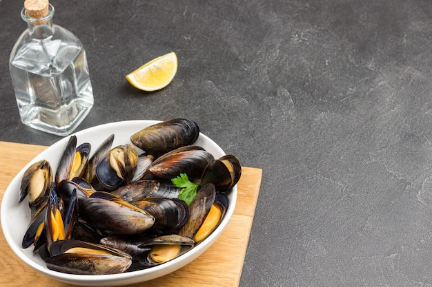 Mussels with open shells in white bowl on cutting board. bottled water and sauce. top view.