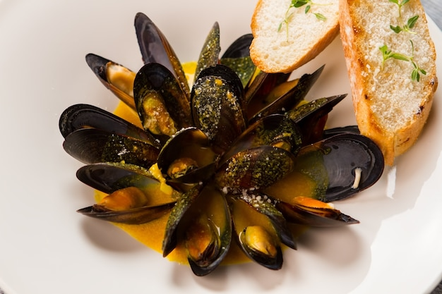 Mussels with yellow sauce. herb and grilled bread. delicacy from french cuisine. seafood dish with thyme.