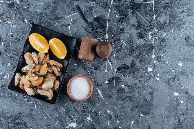 껍질이 없는 홍합과 대리석 배경에 있는 플래터에 얇게 썬 레몬.