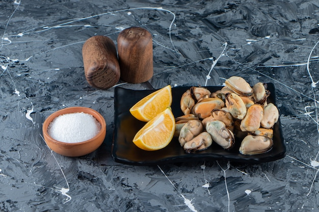 대리석 표면에 플래터에 껍질이 없는 홍합과 얇게 썬 레몬.