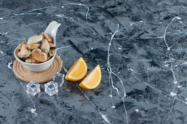 대리석 배경에 얇게 썬 레몬 옆 트리벳에 있는 숟가락에 껍질이 없는 홍합.