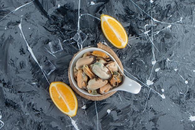 대리석 표면에 얇게 썬 레몬 옆에 있는 삼발이 위에 있는 숟가락에 껍질이 없는 홍합.
