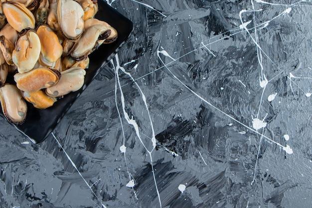 大理石の背景に、大皿に貝殻のないムール貝。