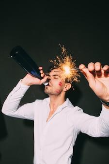 線香花火とボトルからシャンパンを飲むムッシー男