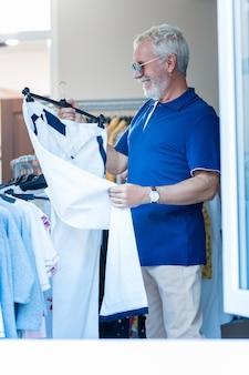 持つ必要があります。スポーツパンツを持って、ショッピングストアに立っている間賞賛を表現する楽観的なファッショナブルな白髪の顧客
