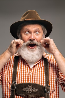 口ひげ。灰色のスタジオの背景に身振りで示す伝統的なオーストリアまたはバイエルンの衣装に身を包んだ幸せな年配の男性。コピースペース。お祝い、オクトーバーフェスト、お祭り、伝統のコンセプト。