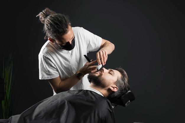 理髪店で髭剃り。検疫コロナウイルスcovid-19でハンサムな男の黒い医療マスクトリムひげのドレッドヘアを持つ床屋。