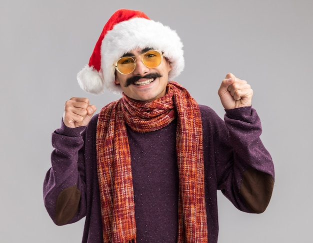 クリスマスのサンタの帽子と彼の首の周りに暖かいスカーフを身に着けている口ひげを生やした男は、白い壁の上に立って幸せで興奮した拳を握り締めます