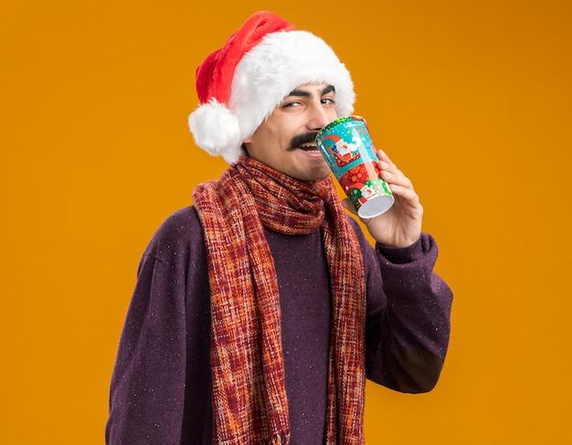 オレンジ色の背景の上に立って幸せで陽気なカラフルな紙コップからジュースを飲む彼の首に暖かいスカーフとクリスマスのサンタ帽子をかぶった口ひげを生やした男