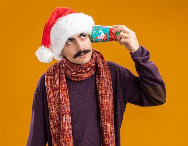 Baffuto uomo che indossa il natale santa hat con calda sciarpa intorno al collo tenendo colorato bicchiere di carta sopra il suo orecchio cercando perplesso in piedi su sfondo arancione