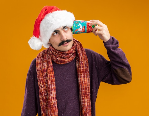 오렌지 배경 위에 의아해 서 찾고 그의 귀에 다채로운 종이 컵을 들고 그의 목에 따뜻한 스카프와 함께 크리스마스 산타 모자를 쓰고 mustachioed 남자