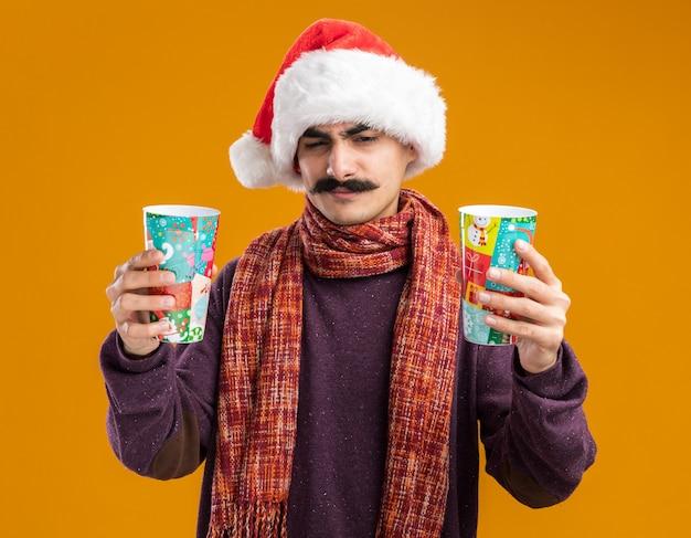 首に暖かいスカーフをかぶったクリスマスサンタの帽子をかぶった口ひげを生やした男は、オレンジ色の背景の上に立っている疑いを持って混乱し、不満に見えるカラフルな紙コップを持っています