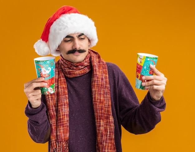 오렌지 배경 위에 서있는 선택을 시도하는 혼란 찾고 다채로운 종이 컵을 들고 그의 목에 따뜻한 스카프와 함께 크리스마스 산타 모자를 쓰고 mustachioed 남자