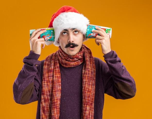 오렌지 배경 위에 의아해 서를 찾는 그의 귀에 다채로운 종이 컵을 들고 그의 목에 따뜻한 스카프와 함께 크리스마스 산타 모자를 쓰고 mustachioed 남자