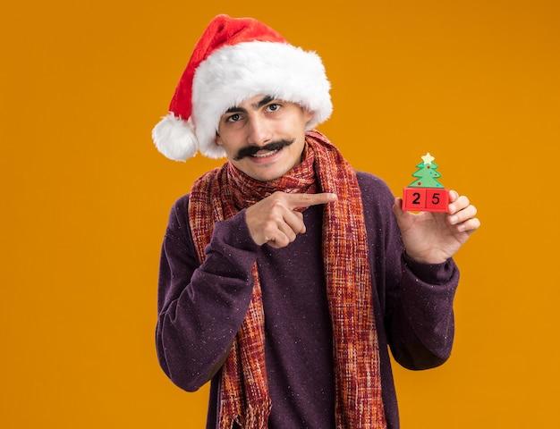 首に暖かいスカーフをかぶったクリスマスサンタの帽子をかぶった口ひげを生やした男は、オレンジ色の壁の上に立って笑っているキューブに人差し指で指している日付25のおもちゃのキューブを保持しています