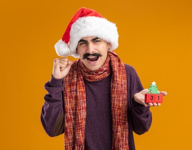 首に暖かいスカーフをかぶったクリスマスサンタの帽子をかぶった口ひげを生やした男は、オレンジ色の背景の上に立って幸せで興奮した新年の日付を握りしめるおもちゃの立方体を保持しています