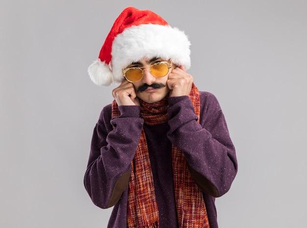 Uomo baffuto che indossa il cappello di babbo natale e occhiali gialli con una calda sciarpa intorno al collo che sembra stressato e preoccupato