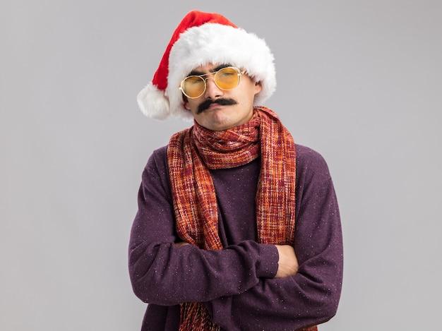 Uomo baffuto che indossa un cappello da babbo natale e occhiali gialli con una sciarpa calda al collo con una faccia seria con le braccia incrociate in piedi sul muro bianco